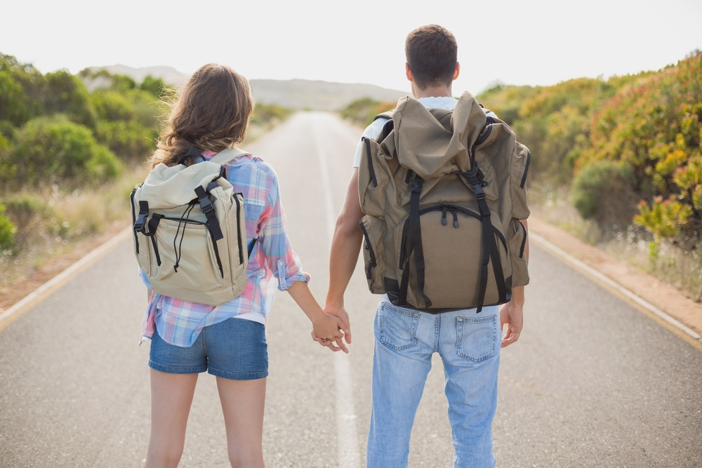 A hiking young couple standing on countryside road